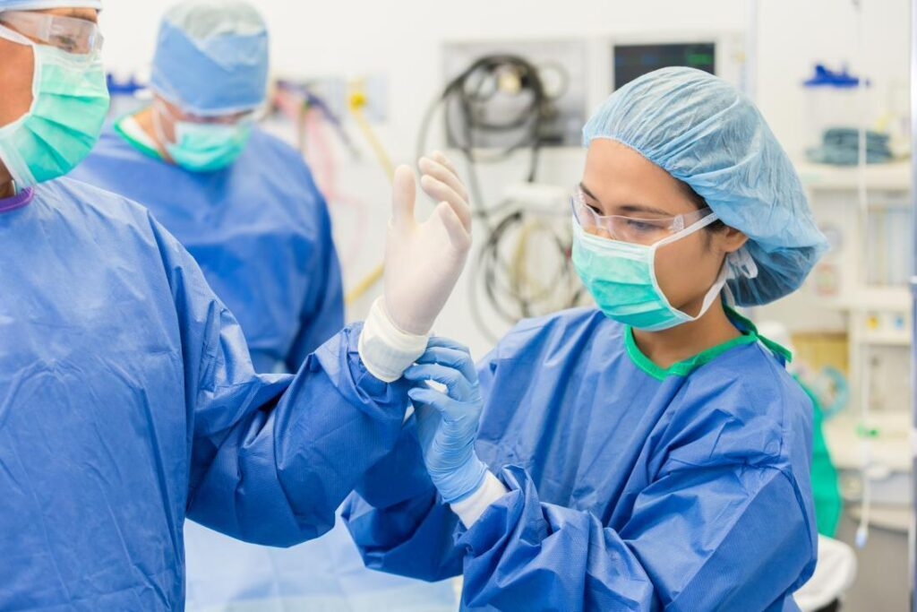 surgeon wearing mask protective eyewear hair net gown and helping other surgeon with sterile gloves before operation 1024x683 - Apa itu Teknik Aseptik?